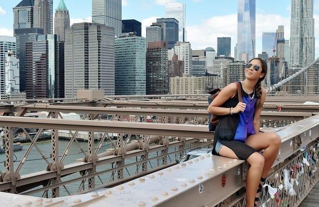 Mujer joven sentada con edificios detrás en New york